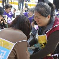 South Koreans opposed to the construction of nuclear reactors cry outside the government complex in Seoul on Friday after a state commission announced the results of a public survey on two stalled reactors. | AP