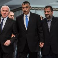 Khaled Fawzi (center), head of Egyptian intelligence, arrives with Fatah's Azzam al-Ahmad (left) and Hamas' Saleh al-Aruri before signing a reconciliation deal in Cairo on Thursday. | AFP-JIJI