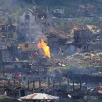 Flames rise near damaged buildings after Philippine government troops cleared the city of Marawi, in the southern Philippines, of pro-Islamic State militants on Monday. | REUTERS