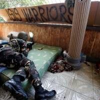 A Philippine soldier lies on a mattress at a position in a house during an assault by government troops on insurgents from the Maute group in Marawi, Philippines, in July. | REUTERS
