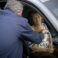 Carmen Hernandez, who lives in a senior living facility that lacks water and electricity in the wake of Hurricane Maria, is checked by a doctor after she fell down, as she sits still for the doctor inside a car parked outside the hospital for lack of space at the hospital, in Bayamon, Puerto Rico, Thursday. Hernandez most desired for people to care for the island's senior citizens in terms of restoring utilities during such high temperatures. 'Don't forget the weakest (people), us elderly folks.' | AP