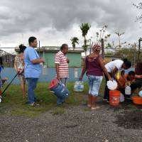 People take water from a tank in Vega Baja, Puerto Rico, on Saturday, due to the lack of water after the passage of Hurricane Maria. | AFP-JIJI