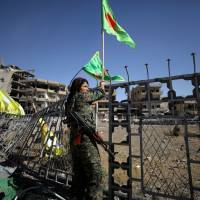 A female fighter of the Syrian Democratic Forces is seen in Raqqa, Syria, on Tuesday. | REUTERS