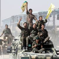 Syrian Democratic Forces fighters celebrate victory in Raqqa on Tuesday. | REUTERS