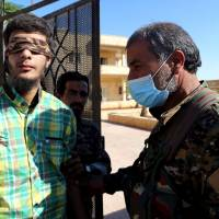 Members of Syrian Democratic Forces escort a blindfolded civilian detainee suspected to be a member of the Islamic State militants in Raqqa, Syria, Thursday. | REUTERS