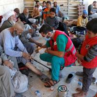Medics treat civilians who got wounded at Raqqa's front line at a mosque in Raqqa, Syria, Thursday. | REUTERS