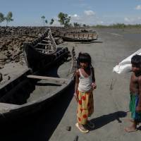 Children collect wood from remnants of some 20 boats that ferried Rohingya refugees fleeing violence in Myanmar that were destroyed by Bangladeshi authorities the night before, at Shah Porir Dwip near Cox's Bazar, Bangladesh, Wednesday. | REUTERS