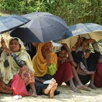 Rohingya Muslim refugees shelter from the sun under umbrellas as they wait for relief aid at the Kutupalong refugee camp in the Bangladeshi district of Ukhia on Wednesday. Myanmar and Bangladesh have agreed to work together to repatriate hundreds of thousands of Rohingya Muslim refugees, officials said, but details remain thin as the humanitarian crisis deepens. | AFP-JIJI
