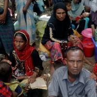 Rohingya refugees who arrived by boat fleeing violence in Myanmar the night before, wait to receive aid at a relief center at Teknaf near Cox's Bazar, Bangladesh, Wednesday. | REUTERS