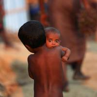 A Rohingya refugee child carries an infant at a refugee camp in Palang Khali near Cox's Bazar, Bangladesh, Wednesday. | REUTERS