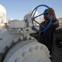 A worker checks pipelines at the Bai Hassan oil field, west of the northern Iraqi city of Kirkuk, on Thursday. | AFP-JIJI