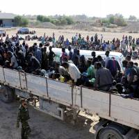 Migrants ride in a truck before they are transported to a detention center, in the coastal city of Sabratha, Libya, Saturday. | REUTERS