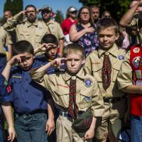 Boy Scouts and Cub Scouts salute during a Memorial Day ceremony in Linden, Michigan, on May 29. | THE FLINT JOURNAL — MLIVE.COM / VIA AP