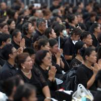 Mourners react as the Royal Urn of late King Bhumibol Adulyadej is carried by the Great Victory Chariot during a royal cremation procession at the Grand Palace in Bangkok Thursday. | REUTERS