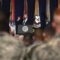 President Donald Trump speaks at Fort Myer in Arlington, Virginia, in August about U.S. strategy in Afghanistan. Trump on Tuesday will call the families of four soldiers killed this month in Niger, the White House says, as Trump again casts doubt on whether his predecessor appropriately consoled the families of military personnel who died in war. | AP