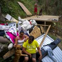 Yadira Sortre and William Fontan Quintero pose with what is left of their belongings, destroyed by Hurricane Maria, while their children build a room to protect themselves from the elements, in the San Lorenzo neighborhood of Morovis, Puerto Rico, Saturday. | AP