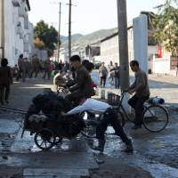 People pull and push a cart through the streets of central Wonsan, North Korea, in October last year. | REUTERS