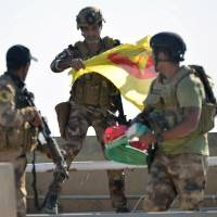 A member of the Iraqi security forces holds a Kurdish flag in Kirkuk on Monday. | REUTERS