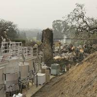 Fermentation tanks stand next to the burned remains of the Signorello Estate winery in Napa, California, on Tuesday. | AP