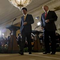 Prime Minister Shinzo Abe and U.S. President Donald Trump walk off stage after a news conference in the East Room of the White House in February.   BLOOMBERG