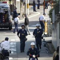 Police investigate the site where a car hit students and a teacher on Wednesday in Hirakata, Osaka Prefecture. | KYODO