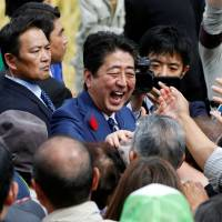 Prime Minister Shinzo Abe shakes hands with his supporters after an election campaign rally in Fukushima on Oct. 10. | REUTERS