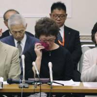 Plaintiffs of a lawsuit seeking damages over health problems caused by asbestos hold a news conference Tuesday in Yokohama following a ruling by the Yokohama District Court that held the government and two companies responsible.   KYODO