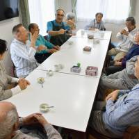 Residents of a care home for people with hearing disabilities in Sapporo chat in sign language during snack time last month. | KYODO