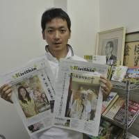 Shinji Matsutani, editor-in-chief of the Christ Newspaper, shows new tabloid versions of the paper at the company in Tokyo's Shinjuku Ward on Sept. 12. | KYODO