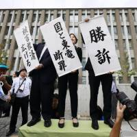 Lawyers representing victims of the Fukushima No. 1 nuclear disaster hold up victory banners in front of the Fukushima District Court on Oct. 10. | KYODO