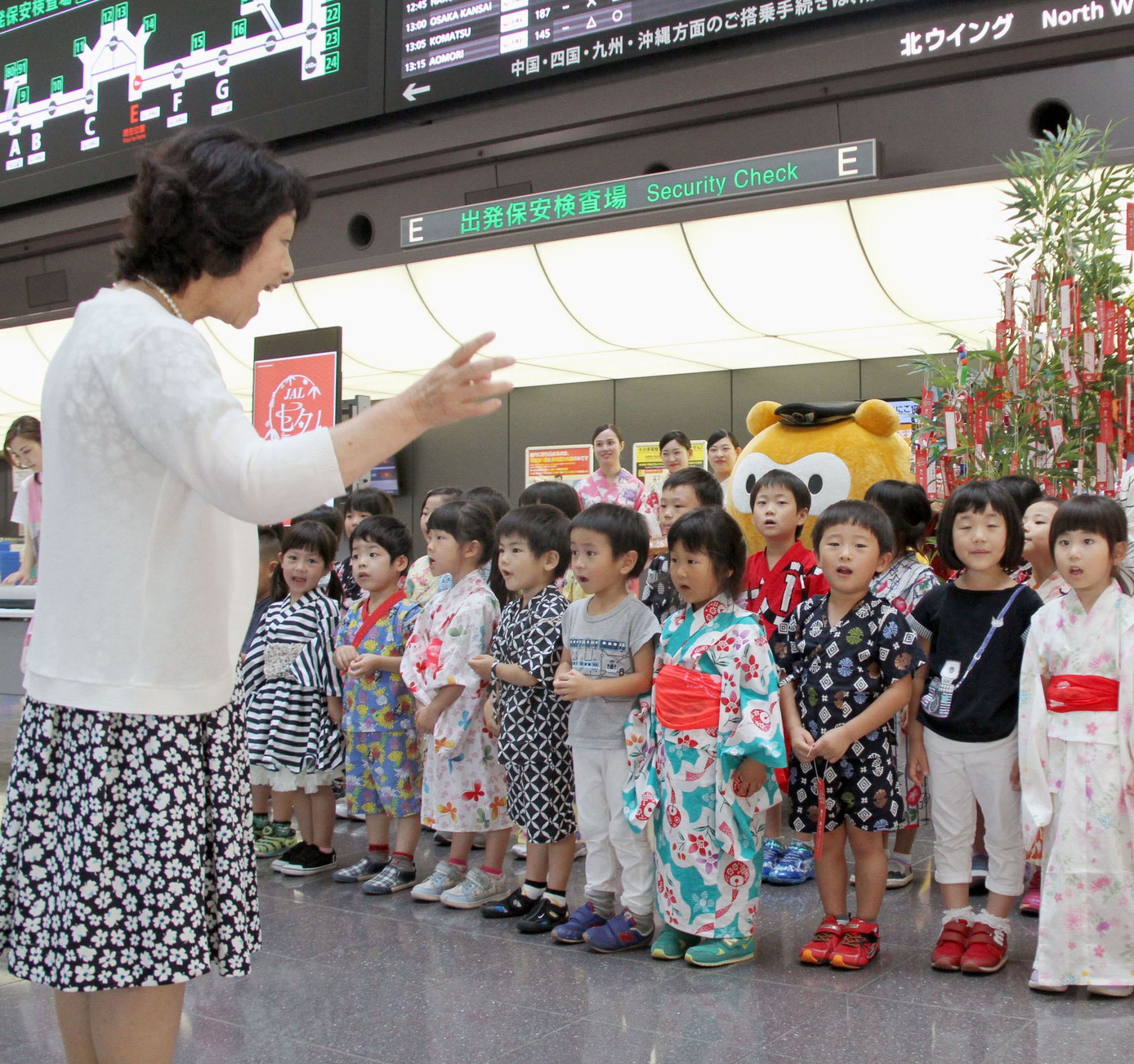 Children in a day care facility inside Haneda airport in Tokyo sing in the departure lobby of the international terminal in July. | KYODO
