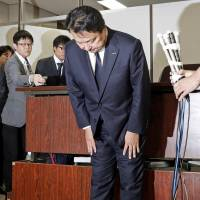 Dentsu Inc.'s President Toshihiro Yamamoto bows in apology Friday in Tokyo following a Tokyo Summary Court ruling which held the company responsible for labor practice violations that resulted in the suicide of an employee. | KYODO