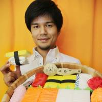 Noriyuki Monda presents an assortment of diapers, baby soaps and bibs arranged to resemble sushi, on Sept. 4. | KYODO
