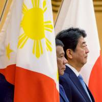 Visiting Philippine President Rodrigo Duterte and Prime Minister Shinzo Abe review an honor guard during a welcome ceremony at Abe's official residence in Tokyo on Monday. | REUTERS