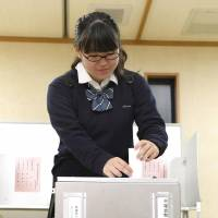 Natsuki Nakagawa, 18, casts the first early vote in the Lower House election Wednesday morning in Mino, Osaka Prefecture. | KYODO