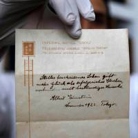 Gal Winner, owner and manager of the Winner's auction house in Jerusalem, displays one of two notes written by Albert Einstein in 1922 on stationery from the Imperial Hotel in Tokyo, on Thursday. | AFP-JIJI