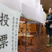 A ballot sign dangles as a prospective voter navigates a polling station in Tokyo during the Lower House election on Sunday. | REUTERS