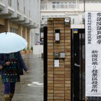 A woman holding an umbrella leaves a polling station in Tokyo during the general election on Sunday. | BLOOMBERG