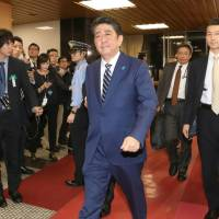 Prime Minister Shinzo Abe enters the Liberal Democratic Party headquarters in Tokyo's Nagatacho district Sunday immediately before voting for the Lower House election closes. | KYODO