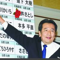 Constitutional Democratic Party of Japan leader Yukio Edano places a paper flower on the name of a winning candidate in the Lower House election in Tokyo on Sunday.  | SATOKO KAWASAKI