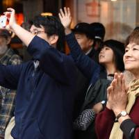 People listen to a Tokyo campaign speech Sunday before the general election on Oct. 22. | AFP-JIJI