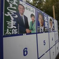 People walk past campaign posters for the upcoming Lower House election in Tokyo on Saturday. | AP