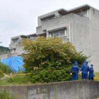 Police Friday conduct an investigation at an apartment in Hitachi, Ibaraki Prefecture, where a man allegedly set a fire and killed his wife and five children. | KYODO