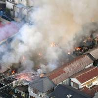 Firefighters battle to keep a blaze from burning down a shopping district in the city of Akashi, Hyogo Prefecture, on Wednesday. KYODO