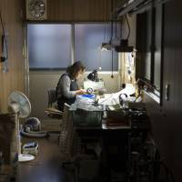 A female worker makes eyeglass temples at Nagai Co. factory in Sabae, Fukui Prefecture. | SHIHO FUKADA FOR BLOOMBERG