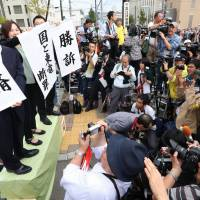 Lawyers for plaintiffs suing the state and Tepco over the 2011 nuclear crisis hold up banners announcing victory in front of the Fukushima District Court on Tuesday. | KYODO