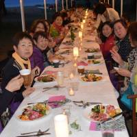Around 40 participants enjoy a sunset dinner by Lake Inawashiro in Fukushima Prefecture during a recent 'glamping' tour. | FUKUSHIMA MINPO