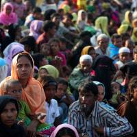As they arrive in Teknaf, Bangladesh, on Oct. 25 after fleeing from Myanmar, Rohingya refugees wait to receive permission from the Bangladesh Army to continue their journey to a refugee camp. | REUTERS