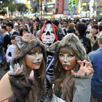Revelers in Halloween attire pose near Shibuya's scramble crossing on Oct. 29 last year. | YOSHIKAI MIURA
