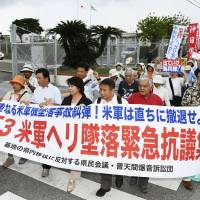 Protesters rally over the crash-landing of a U.S. military CH-53E helicopter, in front of Camp Foster in Kitanakagusuku, Okinawa Prefecture, on Thursday. | KYODO